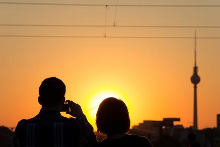 일몰 하늘과 TV 탑의 사진을 찍는 커플