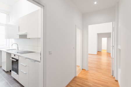empty flat , white kitchen and wooden floor