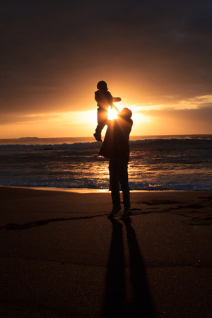 ensuring: happy family at beach - father holding child Stock Photo