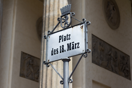 18th: Berlin, Germany - July 20, 2016: Street sign of Platz des 18. Maerz (german for : Square of the 18th march) at Brandenburg gate (Brandenburger Tor) in Berlin. Stock Photo