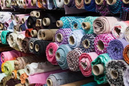 industria textil: fabric rolls at market stall - textile industry background
