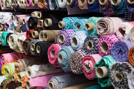 rollos de tela en la parada del mercado de la industria textil - fondo