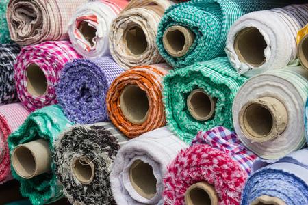 industria textil: rollos de tela en la parada del mercado de la industria textil - fondo