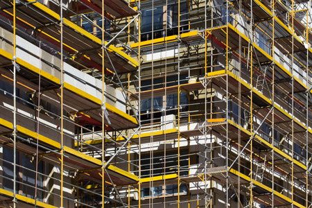 scaffolds: scaffolding on building - building facade with scaffolds