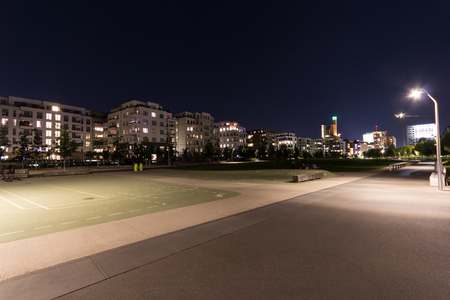 Playground in empty park at night with residential building background