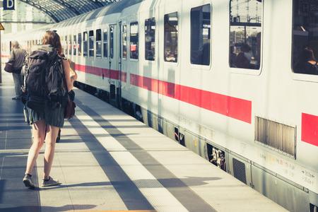 Fille avec sac à dos par derrière debout à plate-forme avant d'entrer dans le train.