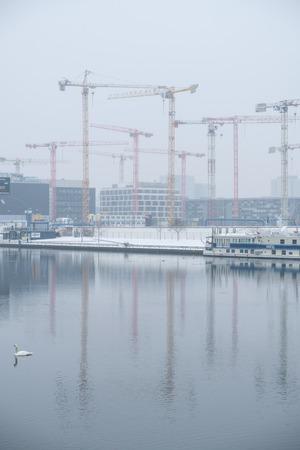 spree: Construction cranes at river Spree in Berlin, near the Mercedes Benz Arena.