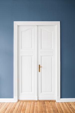 white wooden door, blue wall -  renovated apartment interior Standard-Bild