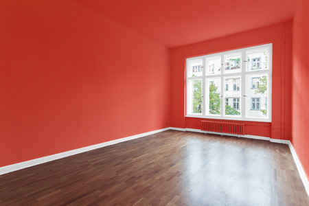 empty room with red walls and wooden floor