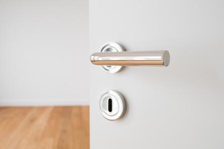 door knob: door handle closeup on open door in new flat