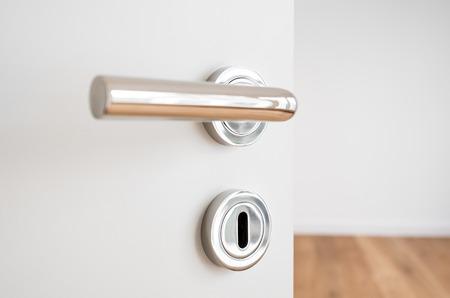 door knob: door handle closeup on open door in new apartment