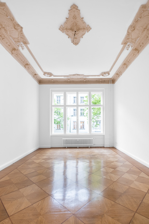 Empty room with parquet floor and stucco ceiling - new renovated flat in old building