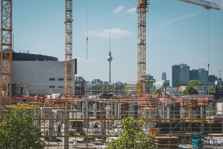 str: Berlin, Germany - may 11, 2017: The tv tower behind the construction site of the East Side Mall, a  shopping mall near the East Side Gallery and next to the Mercedes Benz Arena in Berlin, Germany.