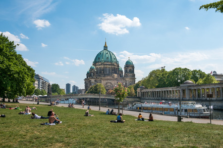 People relaxing on meadow in Monbijoupark on a sunny day in Berlin with the cathedral and tourist boat in background.
