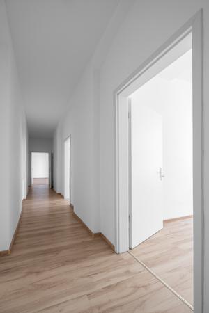 Leerer Korridor, weiße Wände und Holzboden Standard-Bild - 79527484