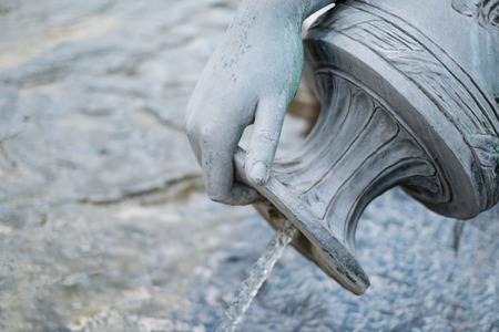antique vase: female hand closeup - bronze statue hand closeup