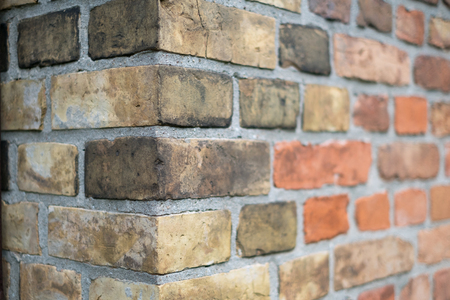 Corner of a vintage brick wall -  stone brick wall edge Фото со стока