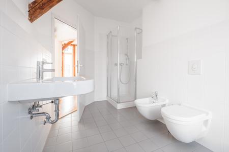 modern bathroom - white tiled bath with shower - Stock Photo