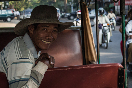 portratit of a smiling man in his tuktuk in Cambodia - 新聞圖片