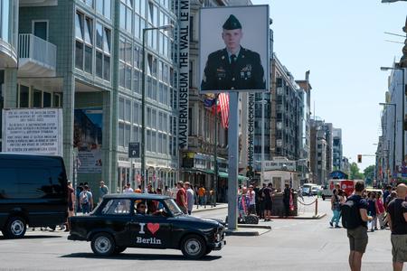 Menschen auf der Straße am Checkpoint Charlie an einem sonnigen Sommertag in Berlin, Mitte. Der ehemalige Grenzkontrollpunkt ist eine der bekanntesten Touristenattraktionen und meistbesuchten Sehenswürdigkeiten Berlins. Editorial