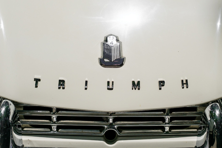TRIUMPH logo  brand name on car front grille closeup at Oldtimer automobile event in Berlin, Germany Editorial