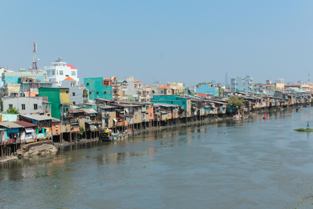 Poor neighborhood huts on stilts at riverside in Ho Chi Minh City aka Saigon, Vietnam Editorial