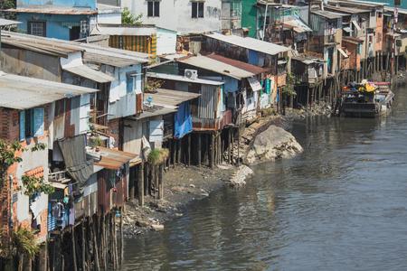 Poor neighborhood huts on stilts at riverside in Ho Chi Minh City aka Saigon, Vietnam Editorial