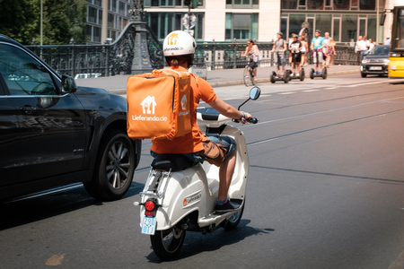 Berlin, Germany - june 2018: A food delivery driver from  Lieferando, a food delivery company, on scooter in traffic in Berlin, Germany