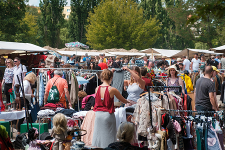Girls looking for clothes and fashion on crowded flea market in Berlin, Germany