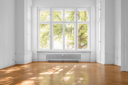 empty room in old apartment building with  parquet floor and big wooden windows - Standard-Bild