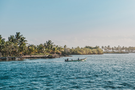 two persons in small motorboat on ocean with tropical palm tree island landscape,