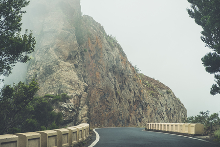 empty road in thick fog in mountain landscape