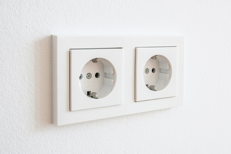 double socket, new electric plug on white wall