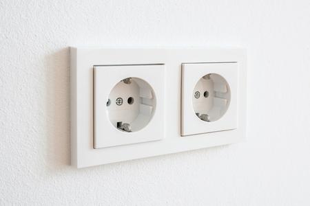 dubbele socket, nieuwe elektrische stekker op witte muur