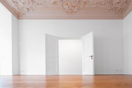 open  door in empty room of historic apartment after refurbishment -