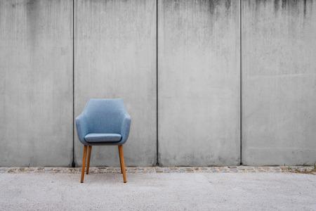 leerer Stuhl mit Betonwandhintergrund auf Bürgersteig -