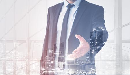 businessman shaking hands, man in suit offering hand for handshake, skyline double exposure