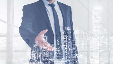 real estate business man  offering hand for handshake , city skyline double exposure