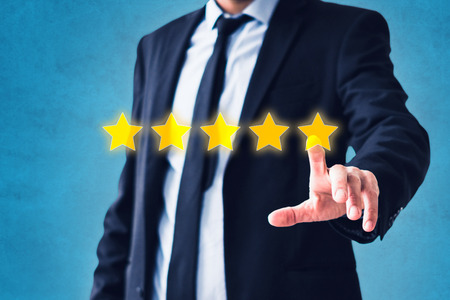 person pointing on 5 star review, costumer feedback concept - five stars rating Stock Photo