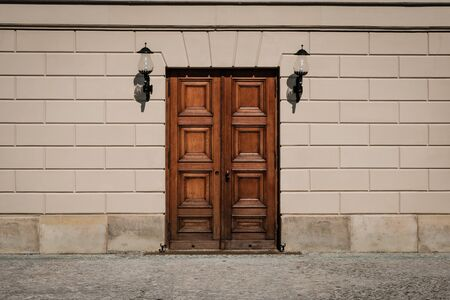 closed wooden door building entrance on street with copy space on wall
