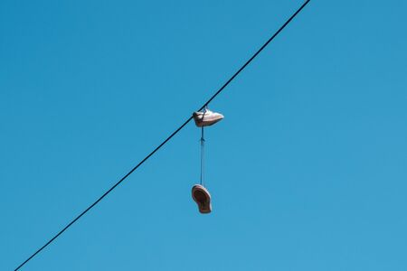 one pair of shoes hanging from a wire  -