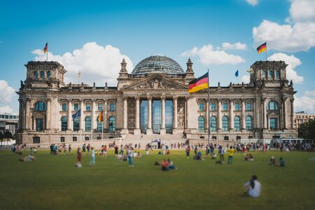 Many people on meadow in front of the Reichstag building, a famous landmark on a sunny, summer day in Berlin, Germany