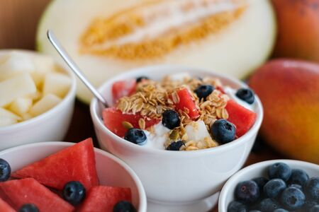 bowl with cereal, fruits and yogurt - healthy breakfast