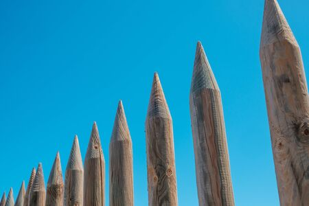 wooden fence made of sharpened wood poles - protective wall