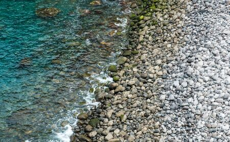 stone beach, pebble stones on ocean coast - nature background