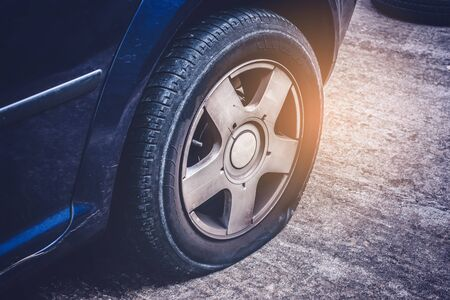 Close up of flat rear tire of a car punctured by screw