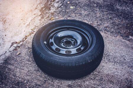 car tire isolated on asphalt floor - car wheel change