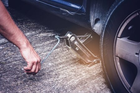 Man lifting car with jack screw for tire changing   of punctured wheel -  tire change oncept