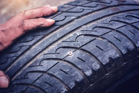 Hands on flat car tire punctured with a screw closeup -