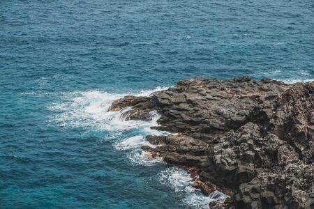 black rock in surf, ocean shore - rocky coast cliff